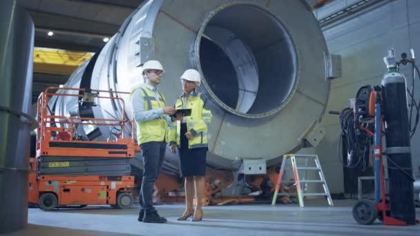 Zwei Schwerindustrie-Ingenieure stehen in der Rohr-Fertigungsfabrik, verwenden digitale Tablet-Computer, diskutieren. Fazilität für den Bau von Öl-, Gas- und Kraftstoffpipelines
