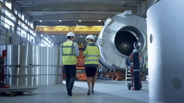 Zwei Ingenieure der Schwerindustrie gehen durch die Rohrfertigungsfabrik, verwenden digitalen Tablet-Computer, diskutieren. Anlage für den Bau von Öl-, Gas- und Kraftstoffpipeline-Transportprodukten