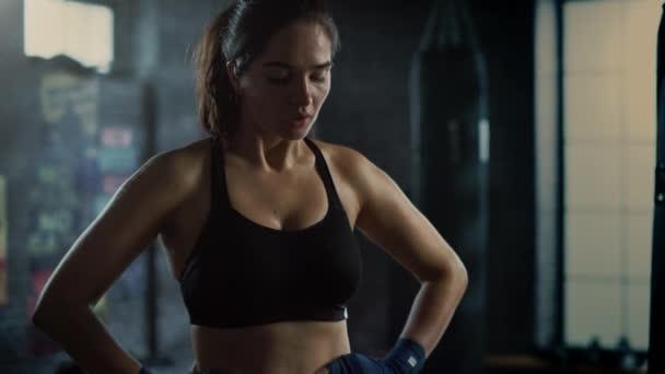Portrét krásné fit bruneta kickboxera stojící v podkrovní tělocvičně s motivačními plakáty. Chytne svůj dech po tréninku intenzivní fitness. Sportovec má na tváři a těle pot.