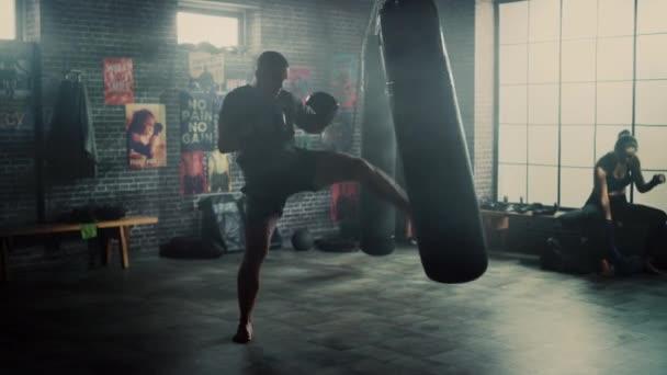 Silný a pohledný mužský kickboxer pracuje v podkrovní tělocvičně s motivačními plakáty na zdech. Mužský atlet se cvičí v boxerském pytli. Je vážný a energický.