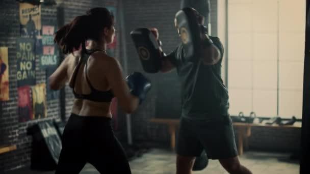 Fit atletická žena kickboxer propíchne děrovací destičky během cvičení v tělocvičně. Je krásná a energická. Silný trenér drží boxovací polštářky. Intenzivní výcvik sebeobrany.