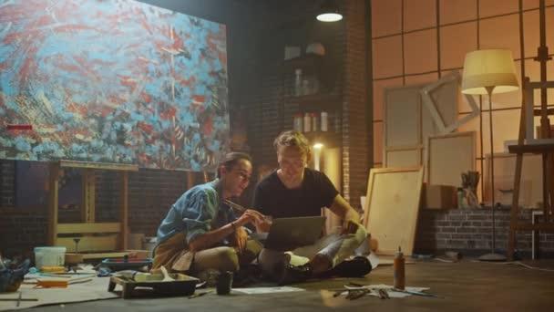 Einige Künstler, die in ihrem Atelier sitzen, benutzen Laptop-Computer, arbeiten an einem Projekt, reden und lächeln. zwei Maler, die im Internet recherchieren und high five, nachdem sie an eine erfolgreiche Idee gedacht haben. Authentische Werkstatt