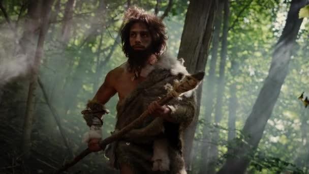 Porträt eines Höhlenmenschen mit Tierhaut und Pelz auf der Jagd mit einem steinernen Speer im Urwald. Prähistorische Neandertaler-Jagd mit primitiven Werkzeugen im Dschungel