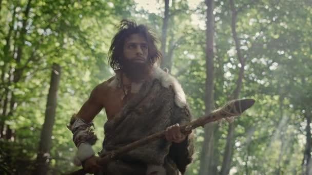 Ősi ősember portréja, amint állatbőrt és szőrméket visel egy kőhegyű lándzsával az őskori erdőben. Őskori neandervölgyi vadász guberálás primitív eszközökkel a dzsungelben