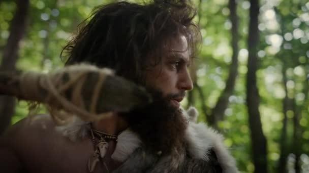 Nahaufnahme Porträt eines Höhlenmenschen, der Tierhaut und Pelz mit einem steinernen Speer im Urwald trägt. Urzeitlicher Neandertaler-Jäger bereit, Speer in den Dschungel zu werfen