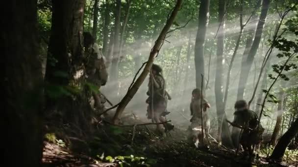 Der Stamm der Jäger und Sammler, die Tierhaut tragen und steinerne Werkzeuge in der Hand halten, erkundet prähistorische Wälder auf der Jagd nach tierischer Beute. Neandertaler auf der Jagd im Dschungel oder beim Wandern. Seitenansicht