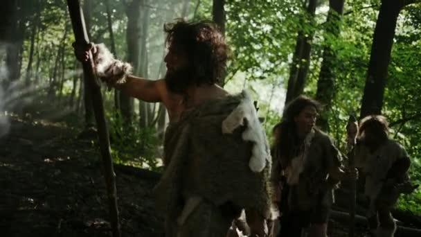 Der Stamm der Jäger und Sammler, die tierische Haut tragen und Steinwerkzeuge in der Hand halten, erkundet den Urwald auf der Jagd nach tierischer Beute. Neandertaler-Familie auf der Jagd im Dschungel oder auf der Suche nach einem besseren Land