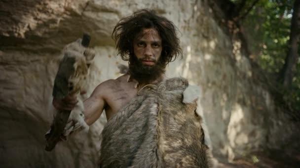 Porträt eines Urmenschen mit tierischer Haut, der einen steinernen Tipped Hammer trägt. Prähistorische Neandertaler-Jäger posieren mit primitiver Jagd im Dschungel. Blick auf die Kamera