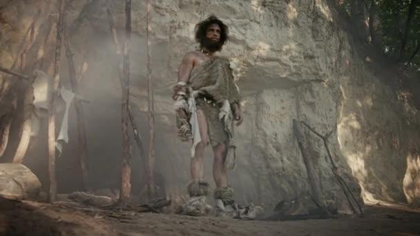 Stammesführer mit Tierfell steht am Höhleneingang und schaut sich um. Familienclanmitglieder bereiten Essen zu, bauen Lagerfeuer, hantieren mit Fellen, arbeiten, jagen. Lebensweise der Neandertaler