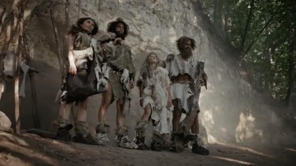 Ein Stamm von vier Jägern und Sammlern, die Tierhaut tragen und Steinwerkzeuge in der Hand halten, posiert am Eingang ihrer Höhle. Porträt zweier ausgewachsener männlicher und zweier weiblicher Neandertaler und ihre Lebensweise