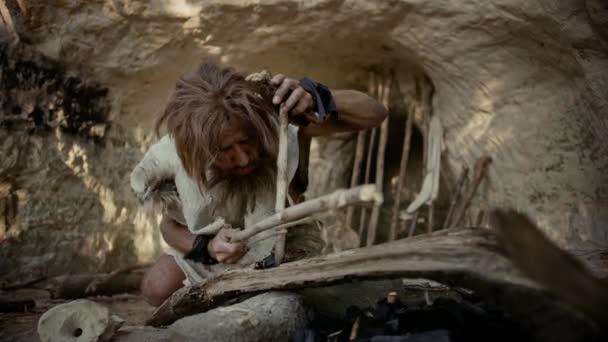Urzeit-Höhlenmensch mit Tierfell versucht mit Bogenbohrmethode Feuer zu machen. Neandertaler entzünden das erste menschengemachte Feuer in der Geschichte der menschlichen Zivilisation. Feuer machen zum Kochen. Zeitlupe Nahaufnahme