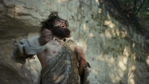 Porträt des Urmenschen, der tierische Haut trägt, schlägt und schreit aggressiv auf die Brust und verteidigt seine Höhle und sein Territorium im Urwald. Prähistorischer Neandertaler oder Homo Sapiens
