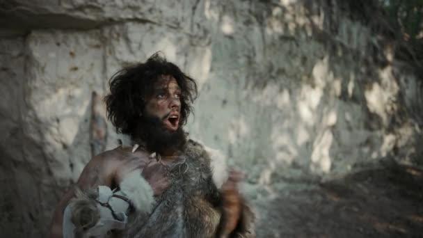 Porträt eines Urhöhlenmenschen mit Tierfell, der seine Höhle und sein Territorium in prähistorischer Zeit verteidigt. Urzeitneandertaler oder Homo sapiens Führer