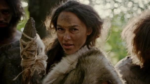 Anführerin und zwei Urhöhlenmenschen in Tierhäuten greifen Feinde mit steinernen Speer an, schreien und verteidigen ihre Höhle und ihr Territorium in der Urzeit. Neandertaler / Homo sapiens Stamm