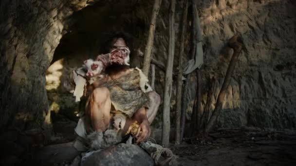 Ur-Höhlenmensch mit tierischer Haut hält Knochen und schlägt damit auf Rock ein. Neandertaler tummeln sich in der Nähe des Höhleneingangs und schaffen vielleicht zufällig erste primitive Werkzeuge oder Waffen.