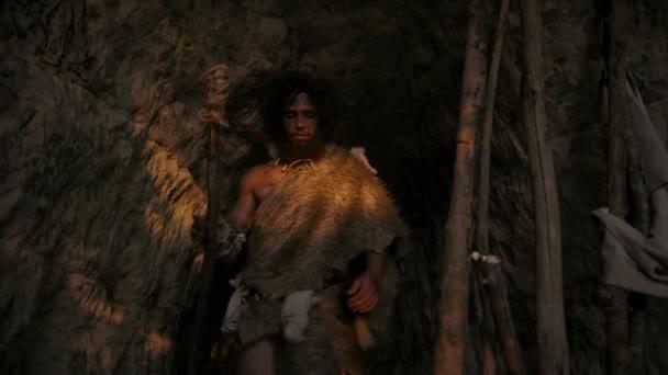 Porträt eines Höhlenmenschen mit Tierfell, der die Höhle verlässt und mit einem steinernen Speer auf die Jagd geht. Der primitive Neandertaler-Jäger / Homo sapiens schielt nach der Sonne, als er aus der Höhle tritt. Kippschuss