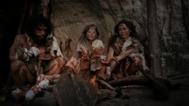 Der Stamm der prähistorischen Jäger und Sammler, die Tierhäute tragen, lebt nachts in einer Höhle. Neandertaler oder Homo-Sapiens-Familie beim Versuch, sich am Lagerfeuer warm zu machen, Hände über dem Feuer zu halten, Essen zu kochen