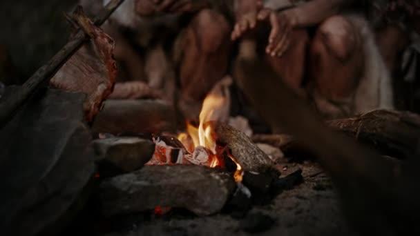 Törzs őskori vadászó-gyűjtögető viselése állat Skins Live barlang éjjel. Neandervölgyi vagy Homo sapiens család próbálok meleg a tábortűz, kezében a tűz, főzés Food. Közeli