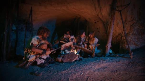 Neandervölgyi vagy Homo sapiens családi főzés állati húst mint Bonfire, majd enni. Törzs őskori vadászó-gyűjtögető viselése állat Skins étkezés a sötét ijesztő barlang éjjel. Nagyítás shot
