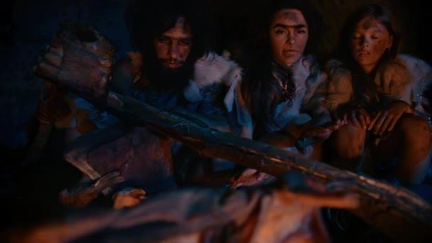 Neandertaler oder Homo sapiens Familie kocht Tierfleisch über dem Lagerfeuer und isst es dann. Stamm prähistorischer Jäger und Sammler in Tierhäuten, die nachts in einer dunklen Gruselhöhle essen. Nahaufnahme