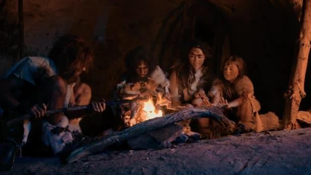 Neandertaler oder Homo Sapiens Familie kocht Tierfleisch über dem Lagerfeuer und isst es dann. Stamm der prähistorischen Jäger und Sammler, die Tierhäute tragen, grillen und nachts Fleisch in Höhle essen