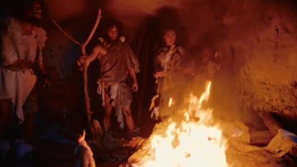 Der Stamm der prähistorischen Jäger und Sammler mit Tierhäuten steht nachts am Lagerfeuer vor der Höhle. Porträt der Familie Neandertaler / Homo Sapiens beim Ritual heidnischer Religion in der Nähe des Feuers