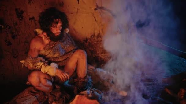 Porträt eines Urmenschen mit tierischer Haut, der in seiner Höhle sitzt und sich am Feuer aufwärmt. Primitiver Neandertaler-Jäger / Homo Sapiens nachts allein in seiner Höhle