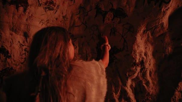 Das primitive prähistorische Neandertaler-Kind mit Tierhaut zeichnet nachts Tiere und abstrahiert sie an die Wände. Erste Höhlenkunst mit Felszeichnungen, Felsmalereien. zurück nach dem Schuss