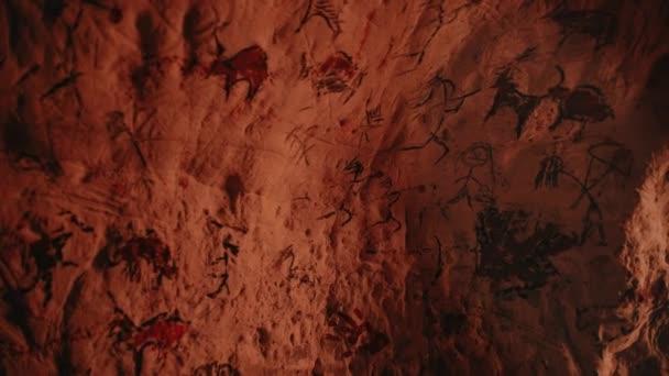 Primitive prähistorische Neandertaler-Zeichnungen von Tieren und Abstracts. Lagerfeuer beleuchtet Wände in der Nacht. Erste Höhlenkunst mit Felszeichnungen, Felsmalereien. Kippbarer schwebender Kamerawinkel