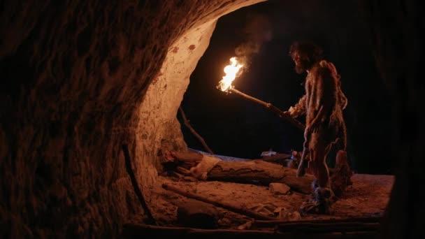 Primeval Caveman viselése állati bőr feltárása Cave éjjel, Holding fáklya tűzzel nézi rajzok a falakon éjjel. Barlang művészet petroglyphs, rock festmények. Oldalnézet