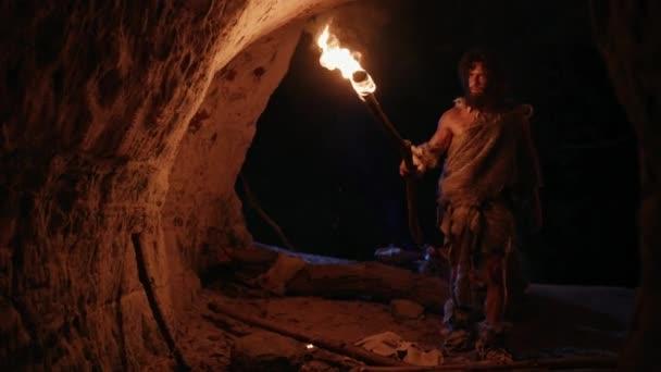 Primeval Caveman viselése állati bőr feltárása Cave éjjel, Holding fáklya tűzzel nézi rajzok a falakon éjjel. Neandervölgyi keresés biztonságos hely tölteni az éjszakát