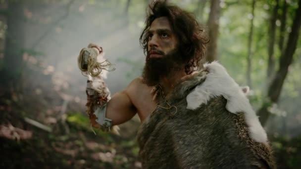 Porträt eines Höhlenmenschen mit Tierhaut und Pelz auf der Jagd mit einem steinernen Speer im Urwald. Prähistorische Neandertaler schleichen sich bereit, Speer in Tier zu werfen