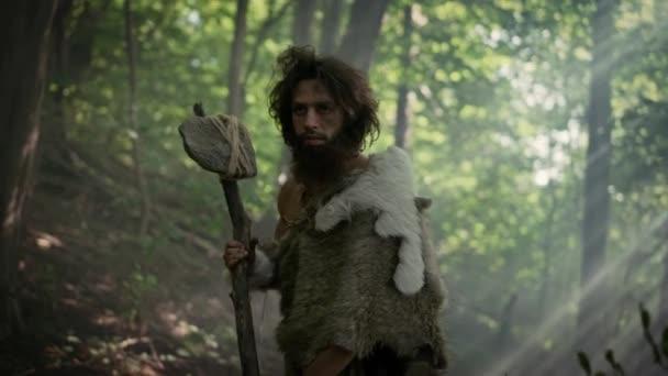 Porträt eines Höhlenmenschen, der Tierhaut und Pelz mit einem steinernen Hammer im Urwald trägt. Prähistorischer Neandertaler bereit zum Angriff auf Beute