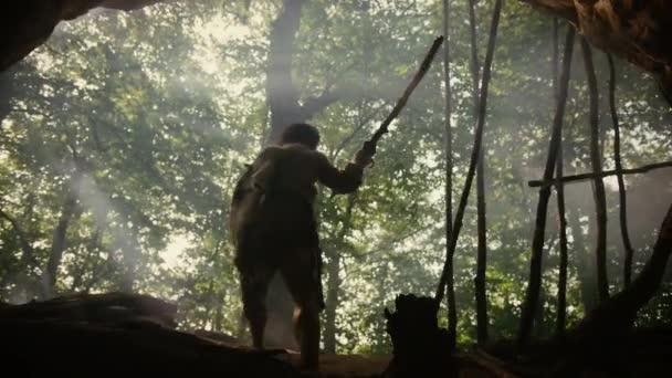 Ur-Höhlenmensch mit Tierhaut hält steingekippten Speer, steht am Höhleneingang und blickt über den Urwald, bereit zur Jagd auf tierische Beutetiere. Neandertaler auf der Jagd im Dschungel