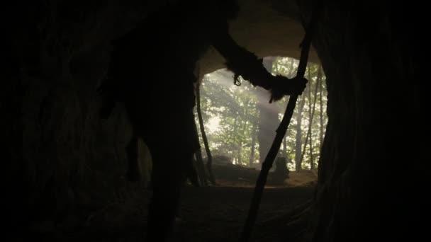 Ur-Höhlenmensch mit Tierhaut und Pelz hält steingekippten Speer in der Hand und kommt aus seiner Höhle in den Urwald. Neandertaler auf Jagd in den Dschungel