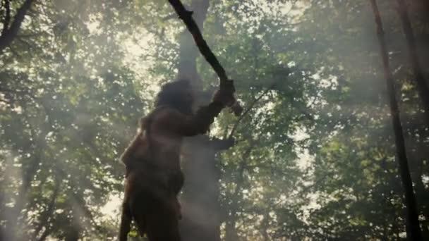 Urzeit-Höhlenmensch mit Tierhaut hält steinernen Speer in der Hand und schaut sich in prähistorischen Wäldern um, bereit für die Jagd auf tierische Beute. Neandertaler auf der Jagd in den Dschungel Bogenschuss in Zeitlupe