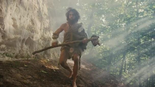 Urzeit-Höhlenmensch mit Tierhaut hält steinernen Hammer in der Hand und erkundet Urwald, bereit zur Jagd auf tierische Beute. Neandertaler auf Dschungel-Jagd. Folgeschuss