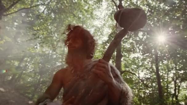 Silhouette des Urmenschen, der Tierhaut trägt, hält steinernen Hammer in der Hand Sieht sich im Urwald um, bereit für die Jagd auf tierische Beute. Neandertaler auf der Jagd in den Dschungel Dramatischer Tieffliegerschuss