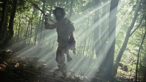 Porträt eines Höhlenmenschen mit Tierhaut und Pelz auf der Jagd mit einem steinernen Speer im Urwald. Primitiver Neandertaler-Jäger bereit, Speer in den Dschungel zu werfen