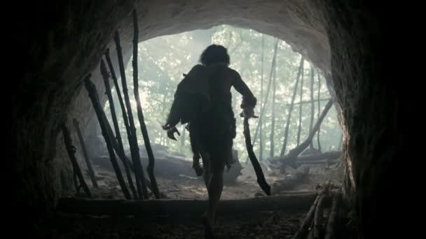 Primeval Caveman viselése állati bőr, szőrmék kő tipped Spear jön ki az ő barlangja őskori erdő Ready to Hunt. Neandervölgyi Going vadászat a dzsungelbe. Következő és portré shot