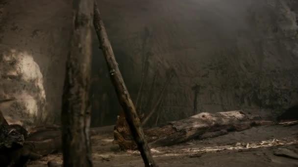 Urzeit-Höhlenmensch mit Tierhaut hält steinernen Hammer in der Hand und schaut sich im Urwald um, bereit für die Jagd auf tierische Beute. Neandertaler auf der Jagd in den Dschungel Schuss von außen