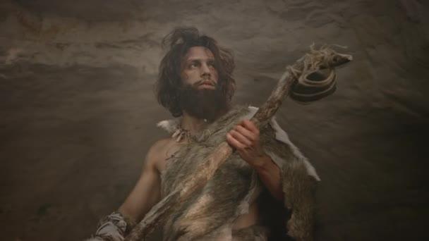 Urzeit-Höhlenmensch mit Tierfell hält Steinhammer in der Hand kommt aus der Höhle und schaut sich in prähistorischer Landschaft um, bereit für die Jagd auf tierische Beute. Neandertaler auf Dschungel-Jagd. Tieffliegerbogenschuss