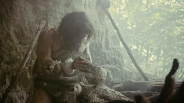 Urzeit-Höhlenmensch mit Tierhaut schlägt mit scharfem Stein auf Felsen auf und stellt primitives Werkzeug zur Jagd auf tierische Beute her. Neandertaler benutzten Handbeil, um den ersten Mühlstein zu schaffen. Zeitlupenaufnahme