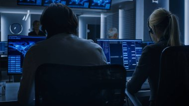 Back View of the Cyber Security Dispatchers Working on Personal Computer Showing Traffic Data Flow in the System Control Room full of Special Intelligence Agents.