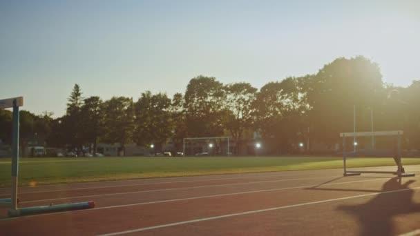 Sportovní fit muž v šedé košili a trenýrkách na stadionu. Skáče přes bariéry v teplém letním odpoledni. Sportovec dělá svou rutinní sportovní praxí. Snímek sledování.