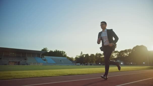 Young Serious Businessman in a Suit Running in an Outdoors Stadium. He Wears Glasses and is Holding a Mobile Phone. Office Worker Chasing Goals. Management Satire. Slow Motion Shot.