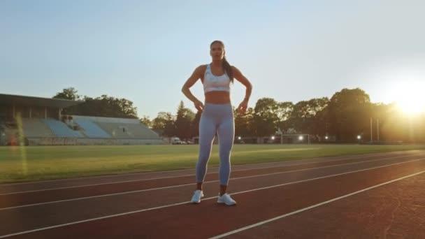 Krásná Fitness žena v světle modré sportovní top a legíny je chytit dech a pózování na stadionu. Trénovala na teplém letním odpoledni a dělala rutinní cvičení.
