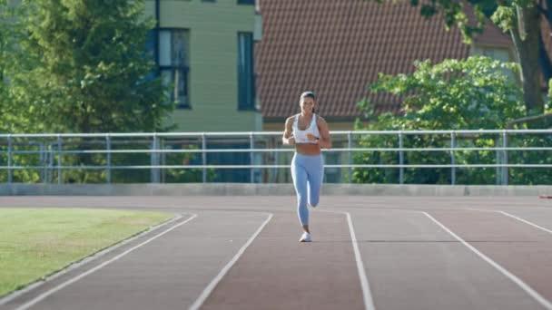 Happy and Smiling Fitness Woman in Light Blue Athletic Top and Leggings Jogging in a Stadium. Běží za teplého letního odpoledne. Sportovec dělá její rutinní sportovní praxi na trati.
