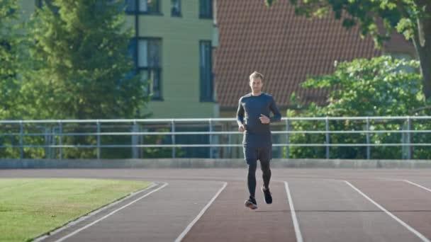 Usmívající se atletický muž v šedé košili a trenýrkách s joggerem na stadionu. V teplém letním odpoledni běží rychle. Sportovec dělá svou rutinní sportovní praxí. Výstřel z pomalého pohybu.