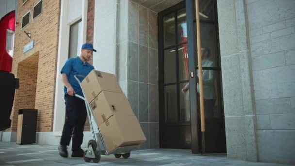 Delivery Man Pushes Hand Truck Trolley Full of Cardboard Boxes Hands Package to a Customer, Who then Signs Electronic POD Device. Courier Delivers Parcel to Man in Stylish Modern Urban Office Area